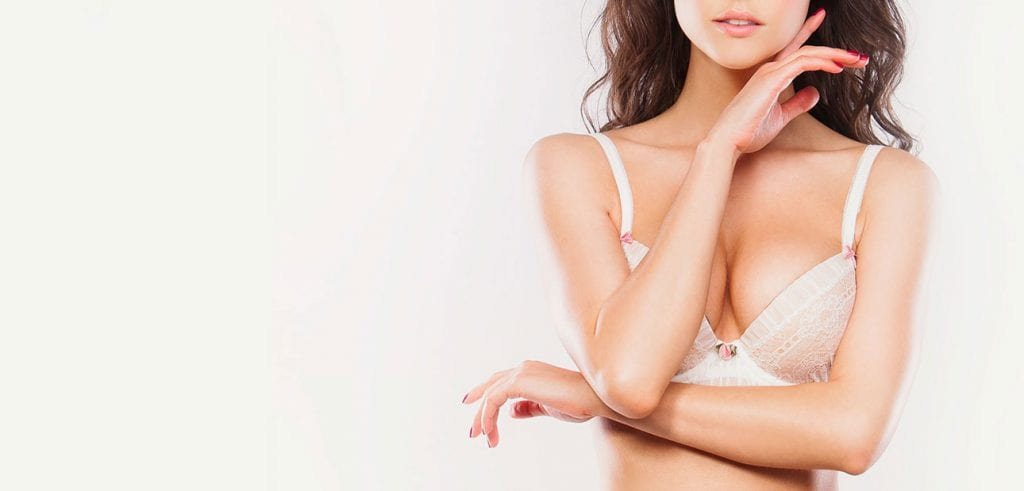 Young woman with enhanced breasts wearing white lace support bra