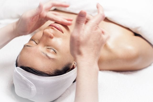 Woman lying on her back getting a facial treatment